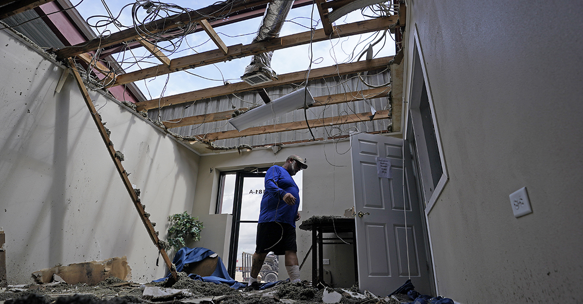 A man walks through destroyed offices with a missing roof in the aftermath of Hurricane Ida