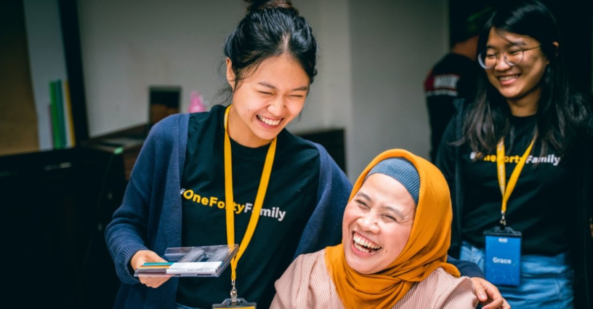 A woman wearing a T-shirt and lanyard and holding markers laughs with another woman in a yellow hijab. In the background, a colleague wears a matching lanyard and T-shirt.