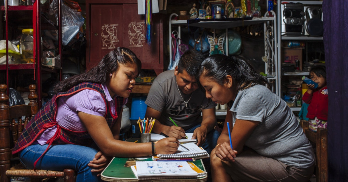 Complex International Grantmaking. Three children sit together at a table and draw in notebooks with colored pencils.