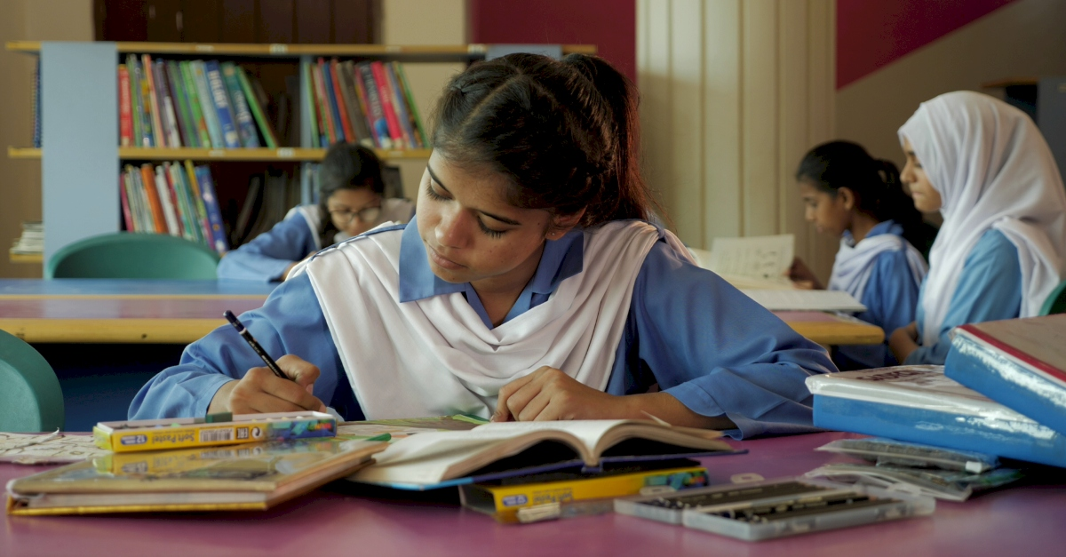 A student in a blue and white uniform looks down while drawing at her desk. Other female students sit behind her, reading.