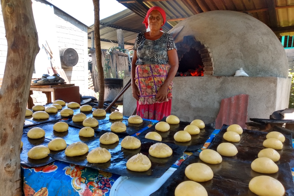 A woman stands behind sheets of unbaked buns. A large cement stove is in lit the background.