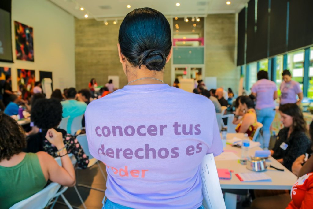 """A woman in a purple t-shirt with the words """"conocer tus derechos es poder"""" on the back stands in front people seated at tables."""