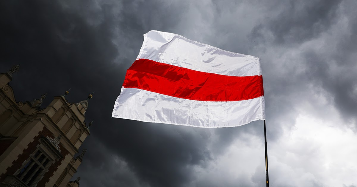 The flag of Belarus with horizontal white and red stripes flaps in the wind. A dark, cloudy sky fills the background.