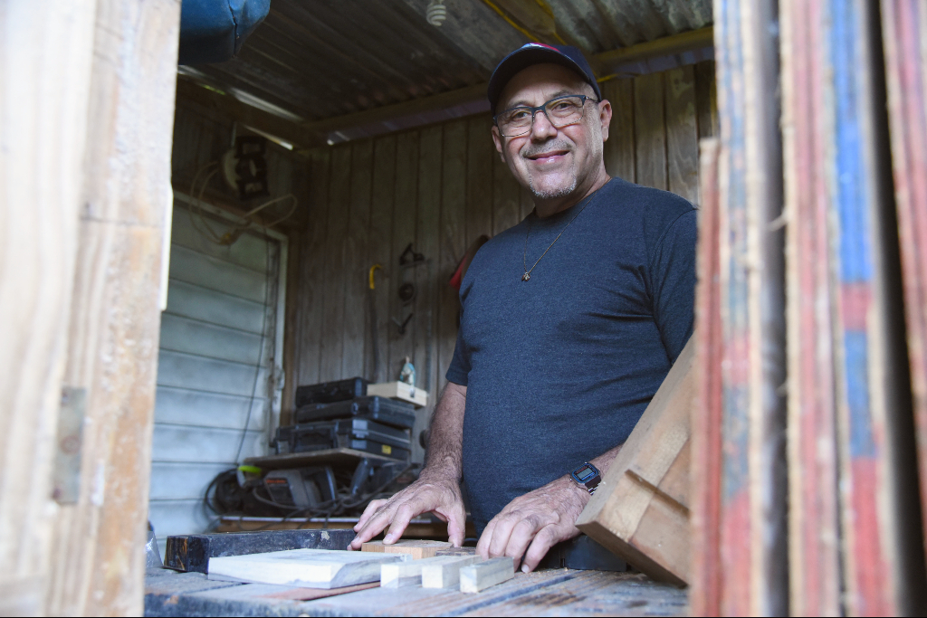 A man in a blue t-shirt and hat touches blocks of wood on a table saw in front of him.
