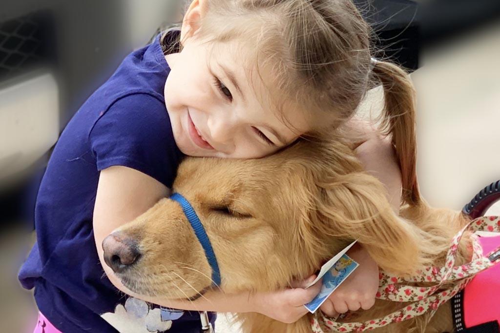 young girl hugs golden retriever