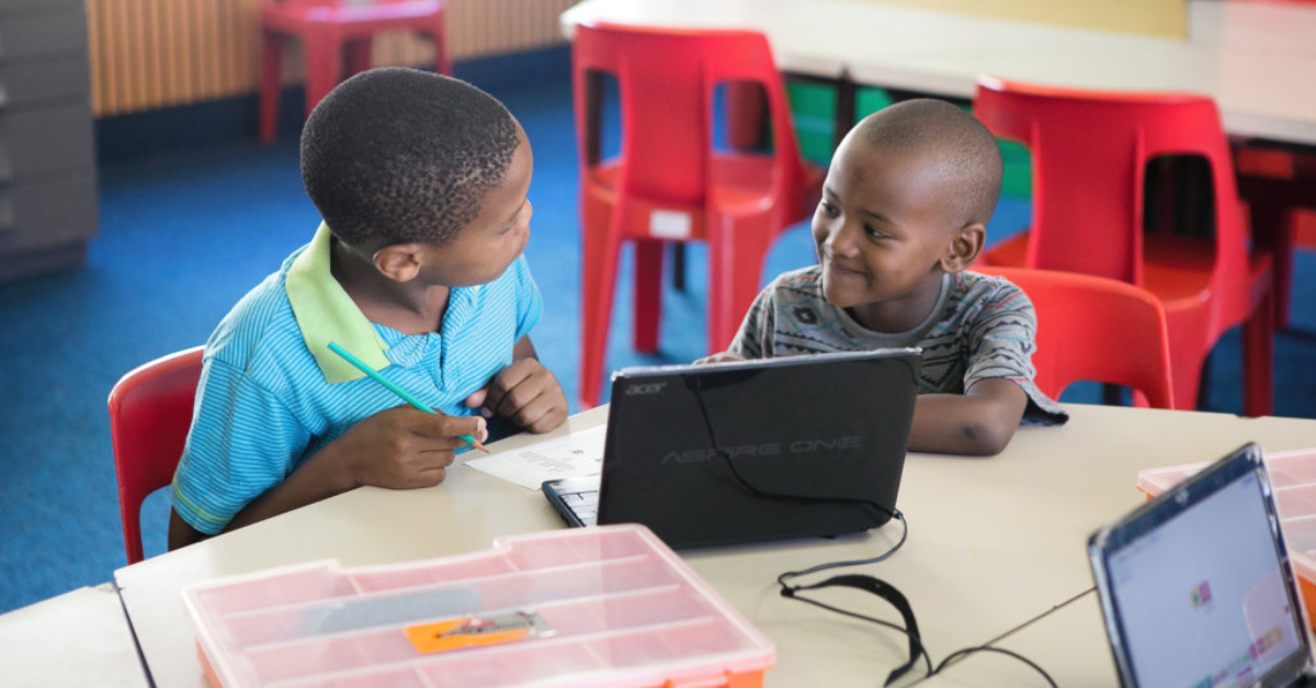 Two young boys sit at a classroom desk behind a laptop. Red chairs and a table are in the background.