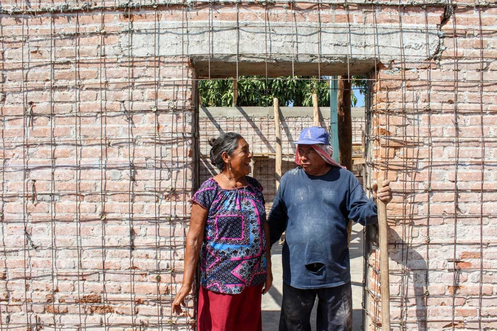 A woman and a man stand in the doorway of a home with exposed bricks and rebar.