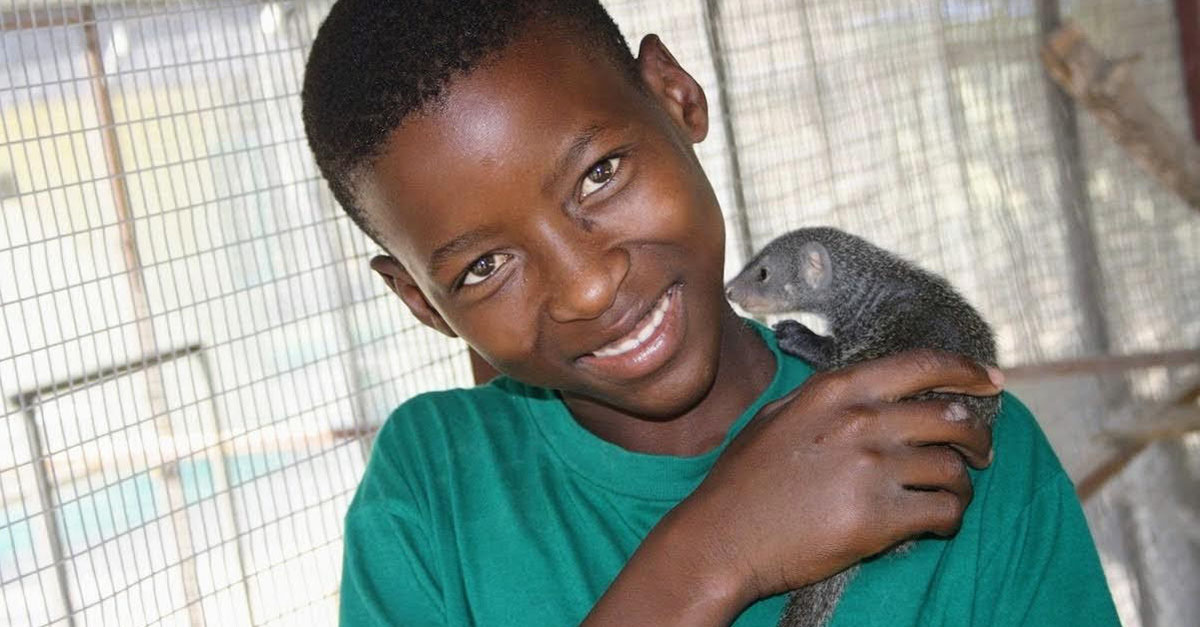 Young boy holding a baby mongoose; A part of DAKTARI's innovative education program teaching local kids about animals and the environment.