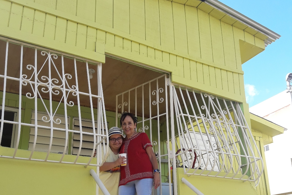 A woman and a young girl stand in the doorway of a yellow house with white wrought iron over the windows and door.