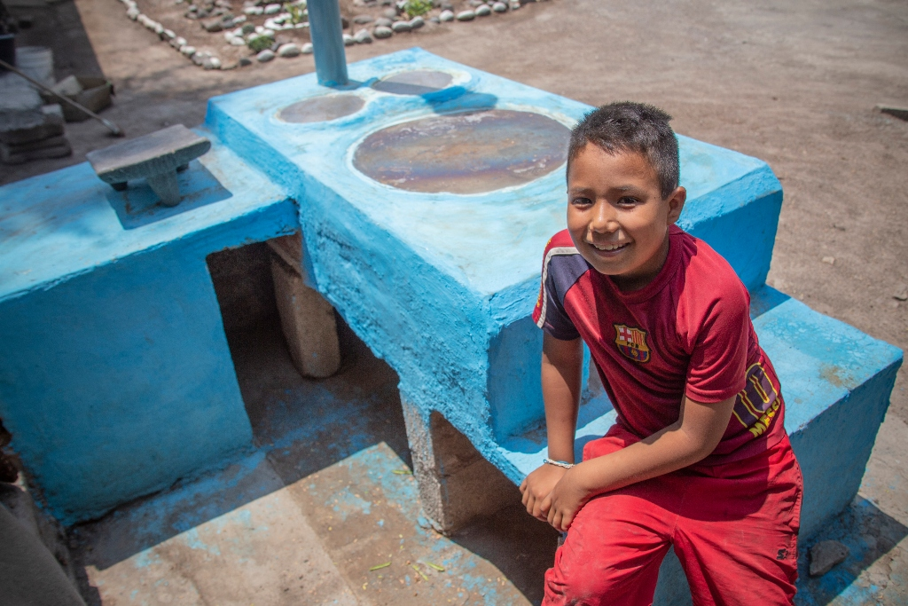 A young boy in a red shirt and pants sits on the side of a blue stove made from mortar