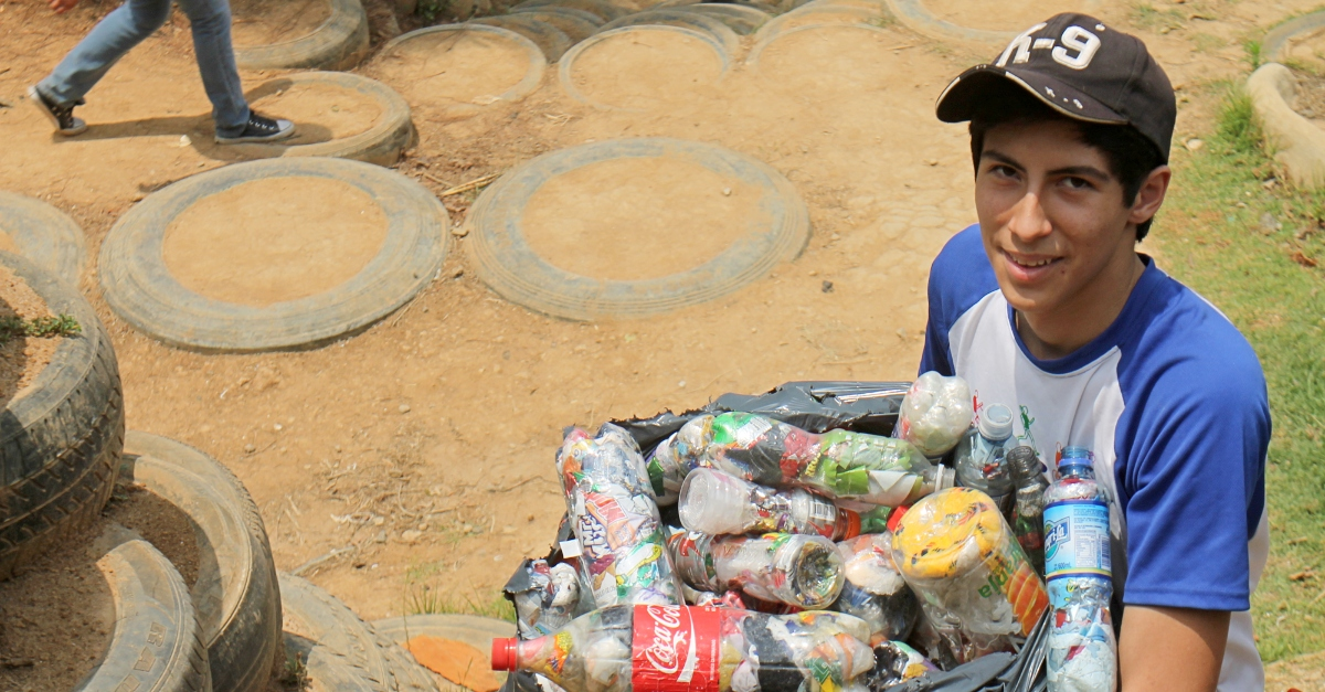 A young boy holds a bag of cans and bottles by a tire wall, part of an innovative education program teaching kids to transform trash into community infrastructure
