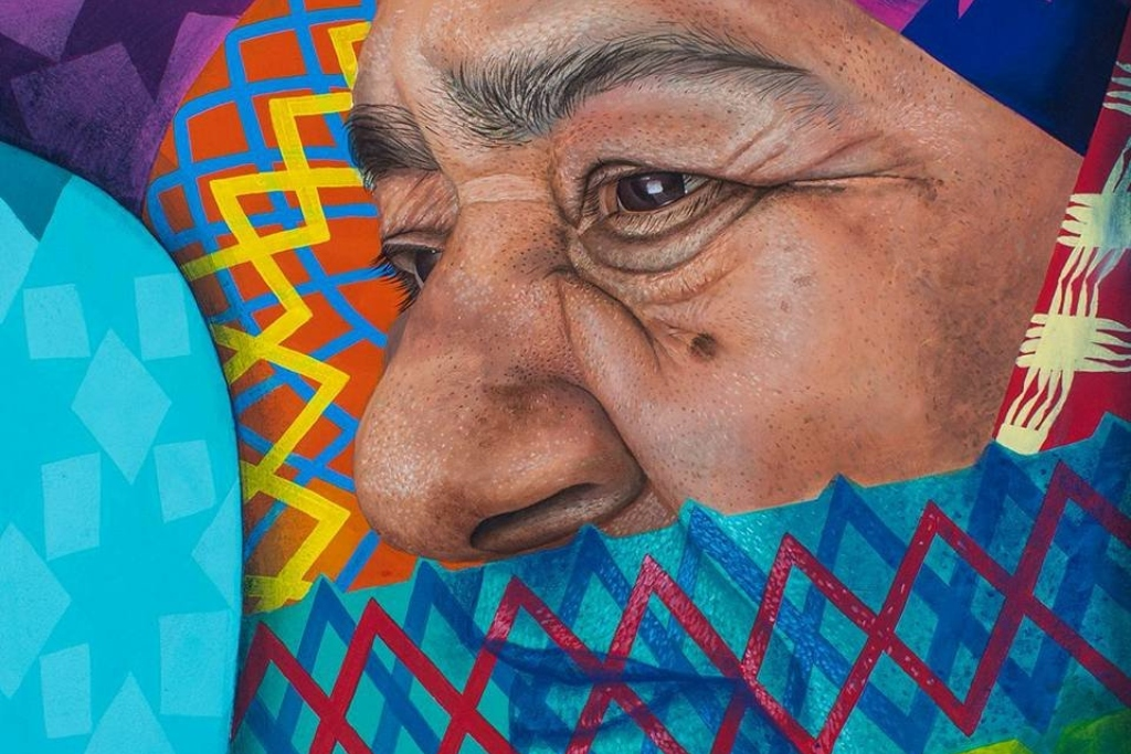 A closeup of a mural showing a woman's profile with her mouth covered by a bright blue and red pattern. Colorful patterns surround her face.