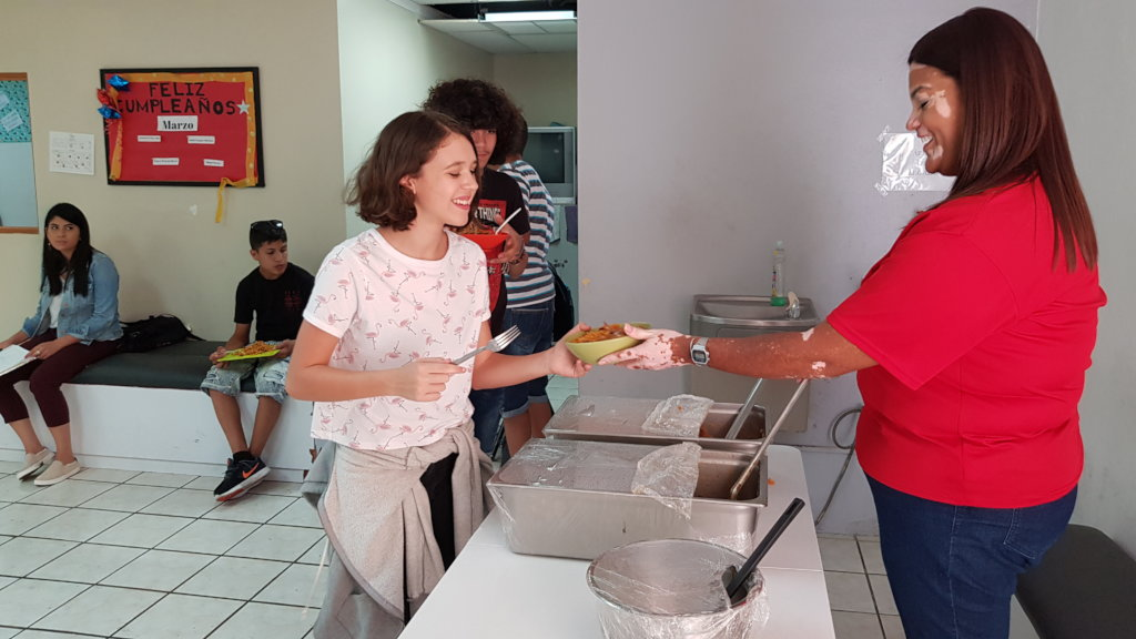 A woman serves a bowl of food to a student in a cafeteria. Another Student stands behind her in line.