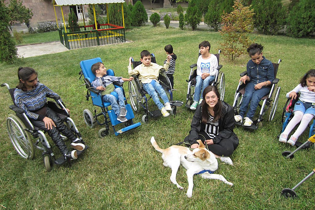 Children in wheelchairs surrounding therapy dog. Dogs with jobs help children with disabilities.