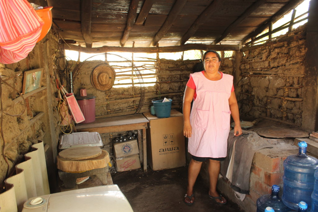 A woman in a pink apron stands in the corner of her kitchen in front of her reconstructed brick stove