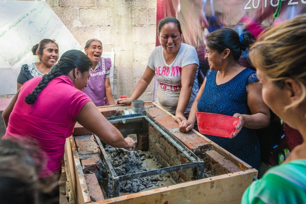 A group of women laugh while rebuilding an oven with bricks and cement.