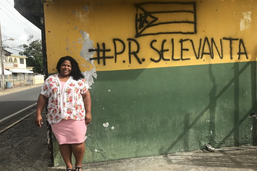 A woman in a pink flowered top and a darker pink dress stands in front of a wall painted yellow and green. The words #P.R. Selevanta and the Puerto Rican flag spray painted at the top of the wall.