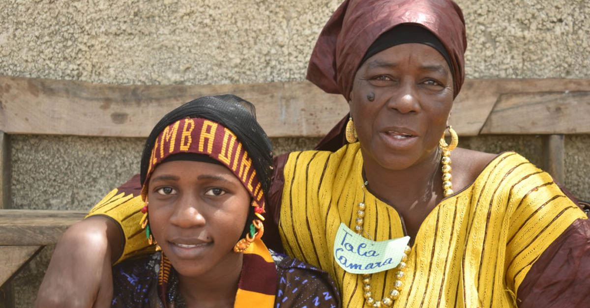 An older woman with her arm around a young girl; part of an innovative education program training grandmothers as teaching assistants