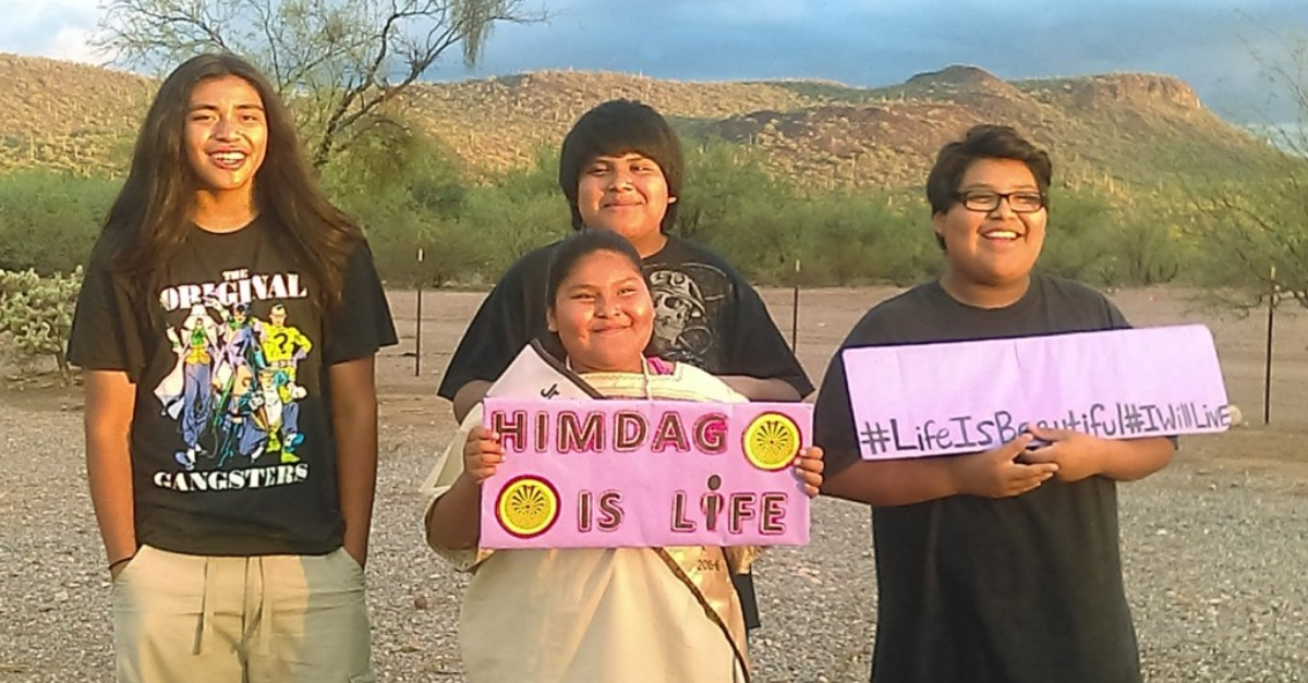 """Four students photographed on the Tohono O'odham Reservation with a sign that says """"Himdag is life"""""""