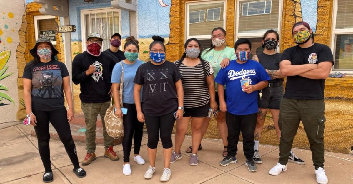 10 young people standing in front of a store with masks, this is a Indigenous-led mutual aid initiative