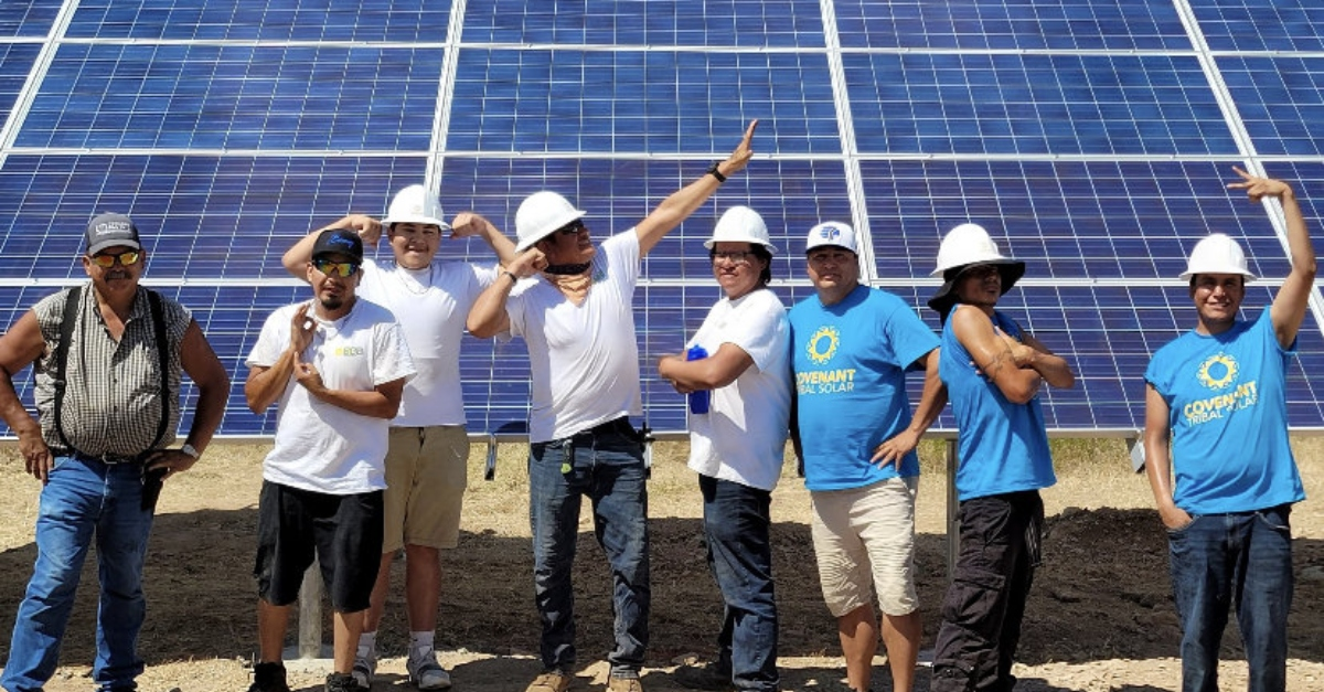 A team posing in front of a solar panel powering a community center during the Indigenous-led training program
