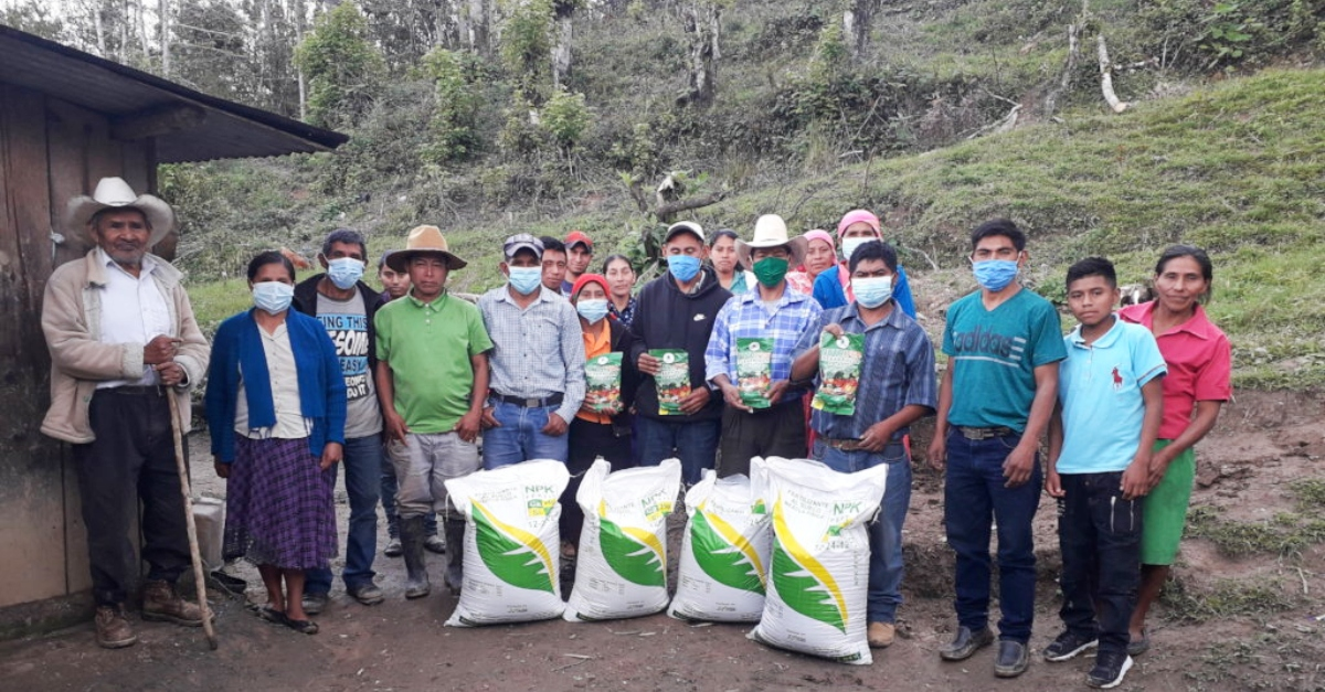 Around 20 people standing in front of new bags of soil and farming materials in Honduras