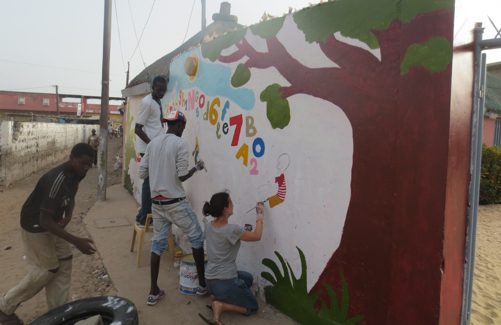 Francesca painting new mural on MDG entrance