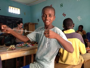 Amadou Diao making a bracelet in Francesca's class