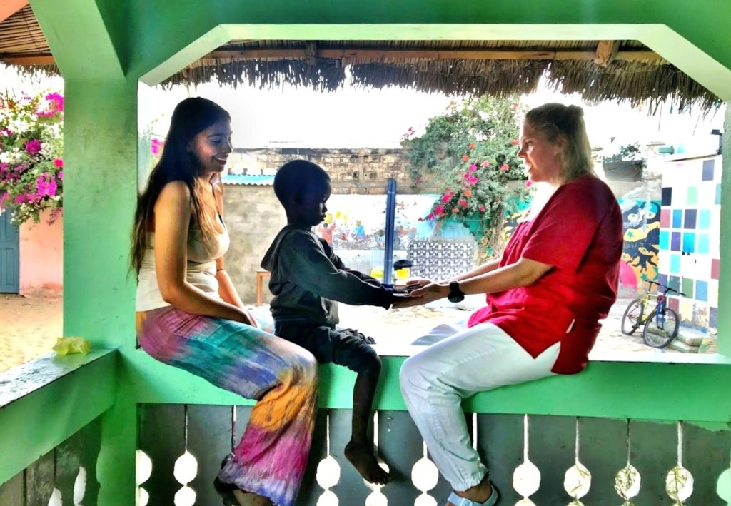 Lise and volunteer Graciela with a talibe child