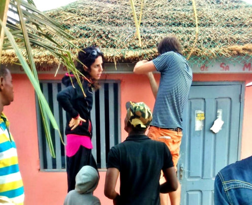 Volunteers repair the library's thatched roof