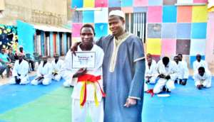 Mamadou receives his new orange belt