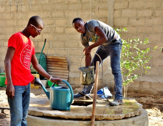 Arouna and Imam draw water from the well