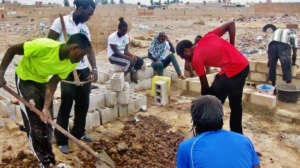 Issa and volunteers dig septic sump for new toilet