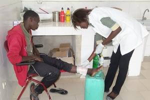 Binta cares for Mamadou Diao's leg