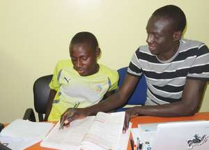 Mapate, MDG administrator, helps Arouna with math