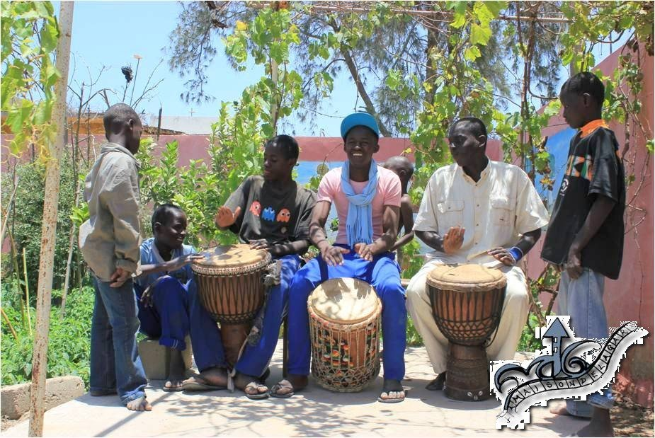 Older talibes relax playing djembe
