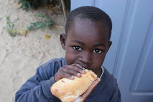 A talibe child enjoys his nutritious baguette