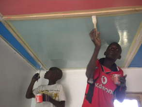 Talibes painting ceiling of new MDG infirmary