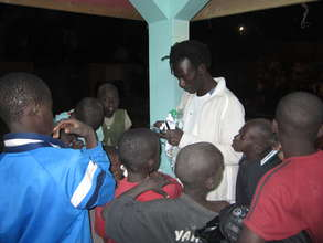 Issa distributing tooth brushes to eager talibes
