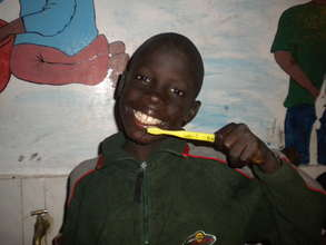 Talibe student brushing his teeth for the 1st time