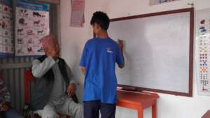 A deaf kids writing something on the board