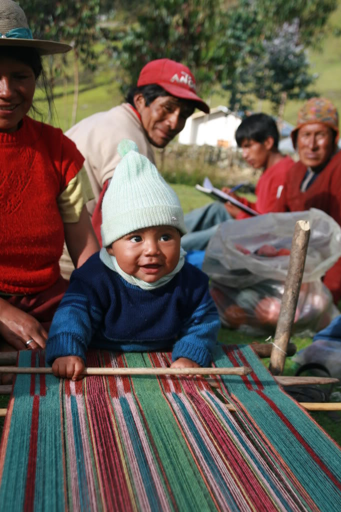 A young child in the Peruvan Andes region playfully tries his hand at the art of Quechua weaving, passed down over thousands of years.