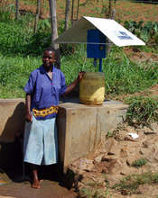 Woman next to community source chlorine dispenser