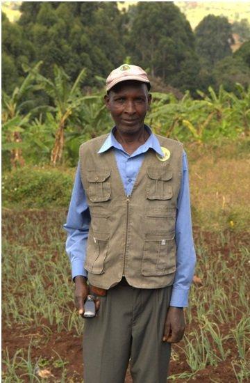 John at his farm, mobile phone in hand.