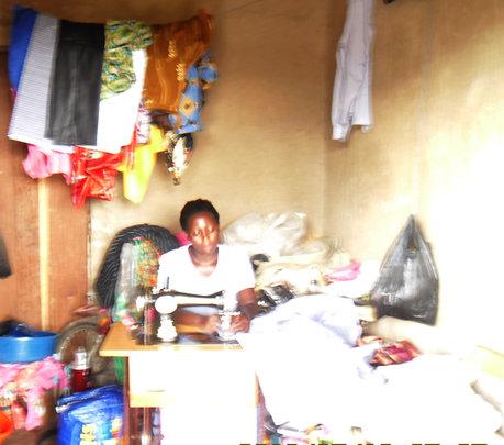 Tailoring graduate at her shop