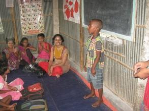 Ms. Tummala listens to a student's poem recitation
