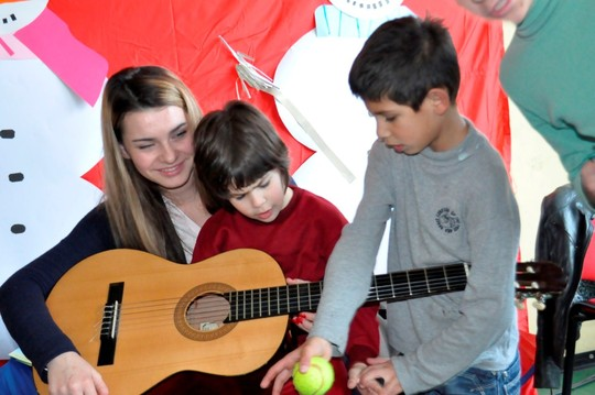 Children at orphanage with their guitar instructor