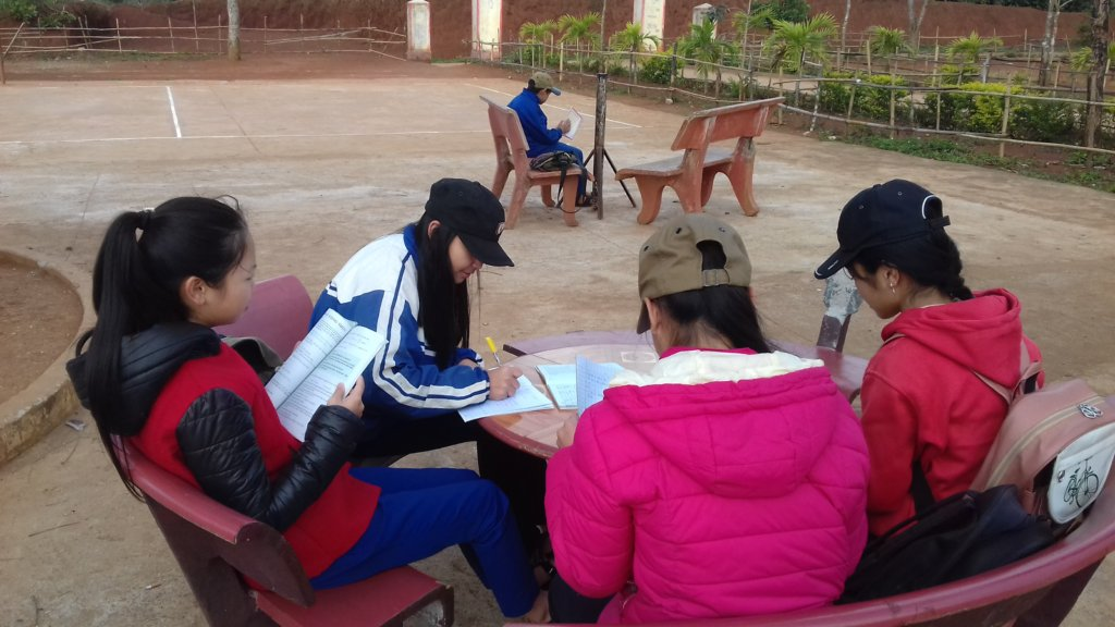 The girls are reading in the school yard