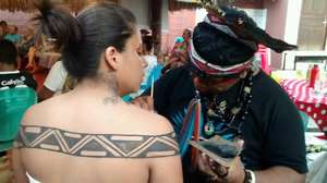 Benicio painting Ruth with indigenous art