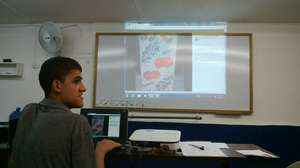 Carlos showing his facebook page at graduation